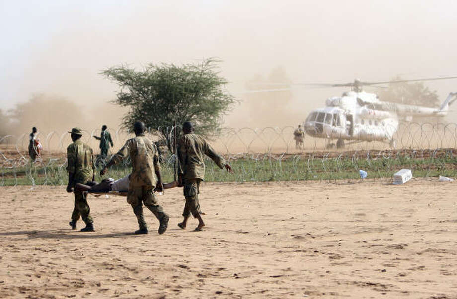 Seriously injured African Union soldiers are carried from Haskanita military camp, in Haskanita,  Sudan, to a waiting helicopter on Sept. 30, to be evacuated for medical treatment.  The camp came under sustained and heavy attack by an armed militia who  overran the base earlier in the day, killing 10 peacekeeping force troops in the attack. Photo: STUART PRICE, AP