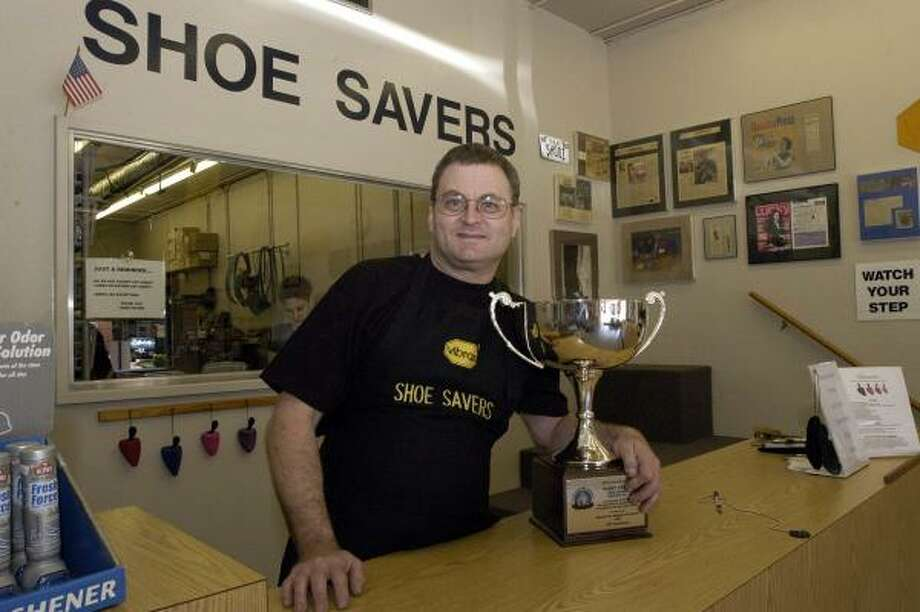 Barry Croft with Shoe Saver shoe repair store poses with the 2004 Grand Silver Cup given by the Shoe Service Institute of America. Photo: Kim Christensen, Special To The Chronicle