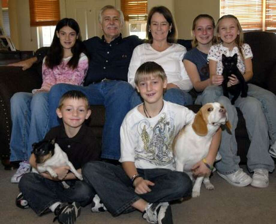 Tom and Shirley Patterson sit in their home with their adopted children — Chance, 6, front left, Devon, 12, Aleus, 12, Marishia, 14, and Beth, 8. Photo: KIM CHRISTENSEN, FOR THE CHRONICLE