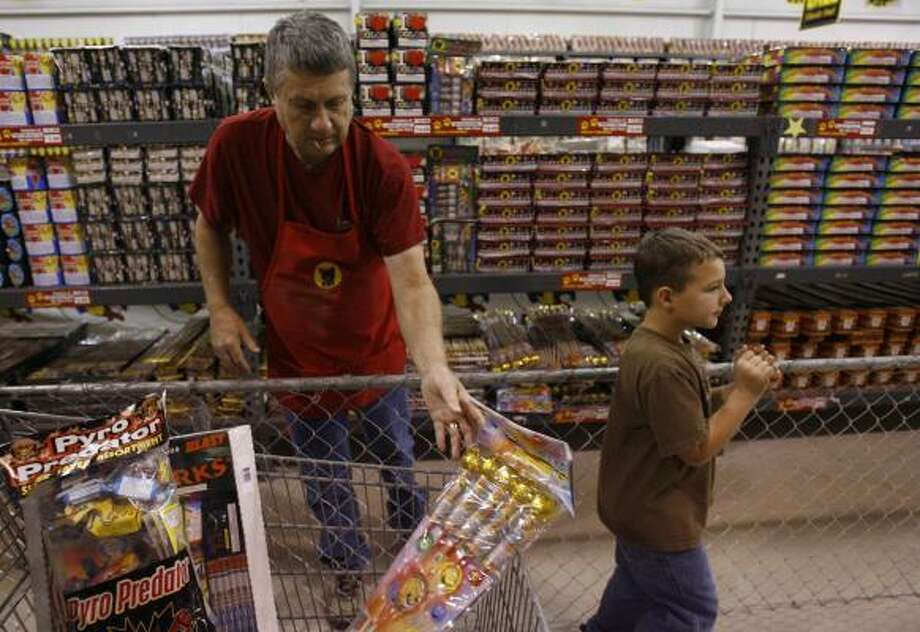 Gene Bell helps Colton Thurman, 7, shop at Top Dog Fireworks on Thursday during the first day of holiday fireworks sales. Photo: MELISSA PHILLIP PHOTOS, CHRONICLE