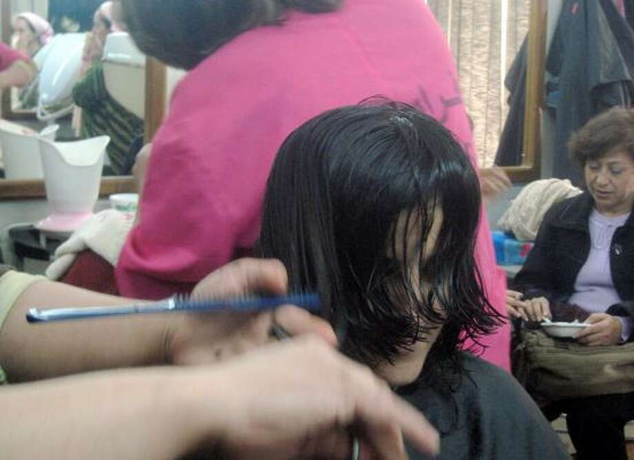 A hairdresser works in a shop in eastern Baghdad that is considered relatively safe, unlike Sunni-dominated west Baghdad. Photo: DIAA HADID, ASSOCIATED PRESS