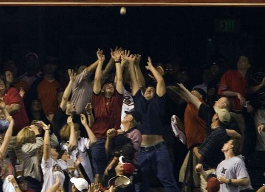 Fans in the Crawford Boxes reach to try to snag a home run off the bat of Pittsburgh's Xavier Nady that tied the game in the ninth inning Monday. Photo: SMILEY N. POOL, CHRONICLE