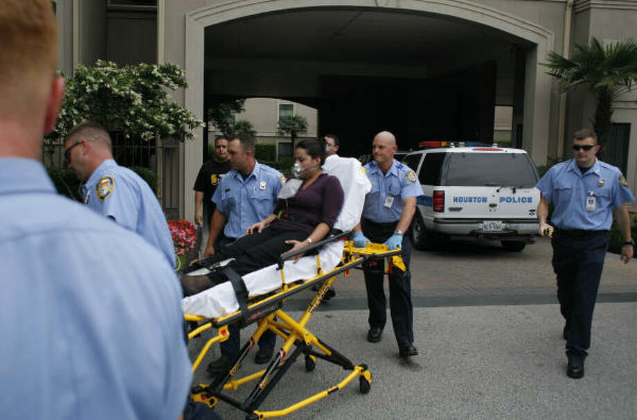 Houston Fire Department paramedics depart with a woman today from the scene of a double shooting at The Post Oak at Woodway luxury apartments. Police said the shooting was a murder-suicide. Photo: Steve Ueckert, Chronicle