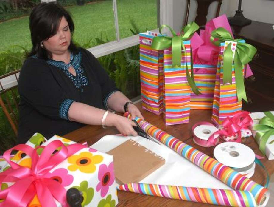 Leigh Williams, owner of Leigh Williams Lifestyle Management, wraps gifts for a client. While most of the clients of Williams' 14-year-old business tend to be wealthy, more less-than-affluent professionals are hiring part-time concierges to help them get through the day. Photo: MEGAN TRUE, CHRONICLE