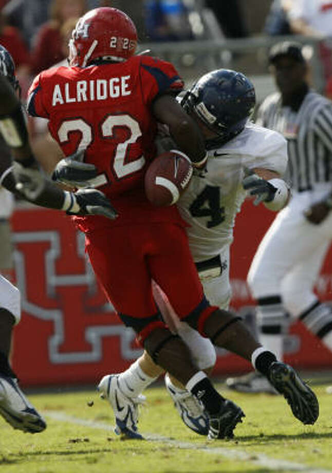 Rice's Justin Abt forces a fumble by Houston's  Anthony Alridge. Photo: Kevin Fujii, Chronicle
