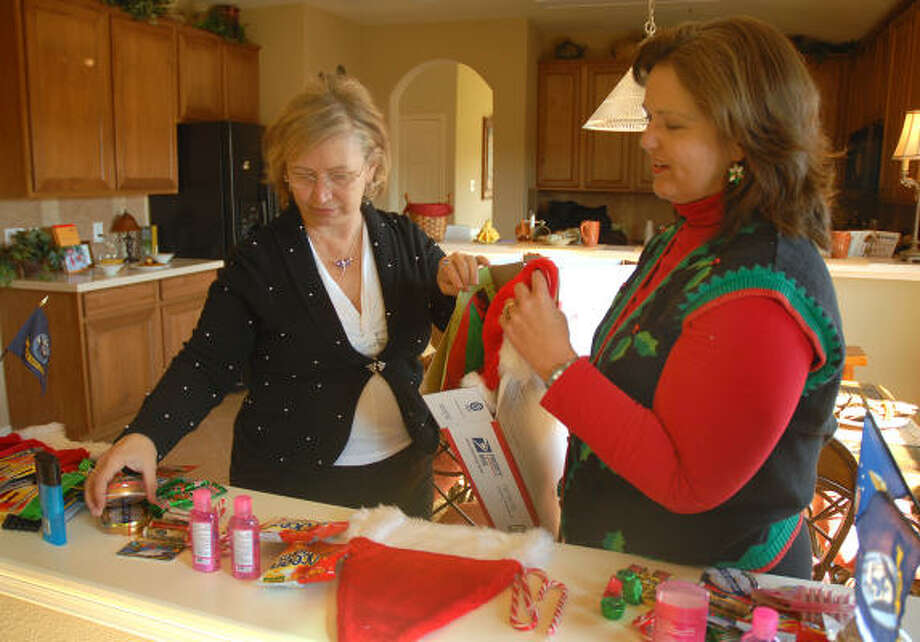 Montgomery County Women's Council of Realtors members Linda Daves and Karen Carlton prepare a package for the Montgomery County Cares' Operation Holiday for Heroes. The group shipped more than 900 gift packages for soldiers. Photo: David Hopper, For The Chronicle