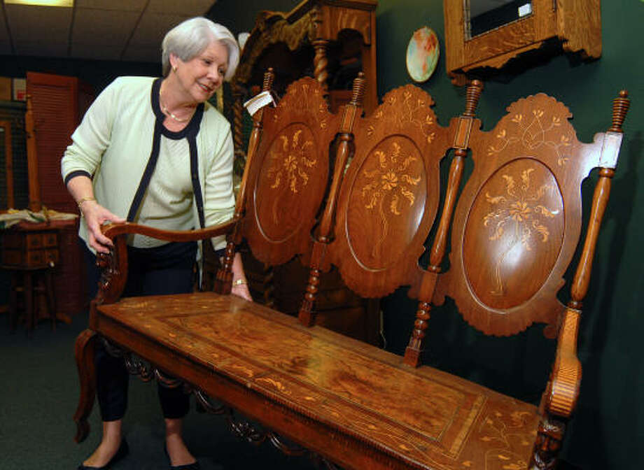 Cathy Reeves of Montgomery prepares items for The Friendship Center Antiques Show and Sale to be held in Montgomery May 5-6. She is moving a late-1700s Italian satinwood bench to be taken to the show. She is in the Crossroads Antiques store in Conroe. Photo: David Hopper, For The Chronicle