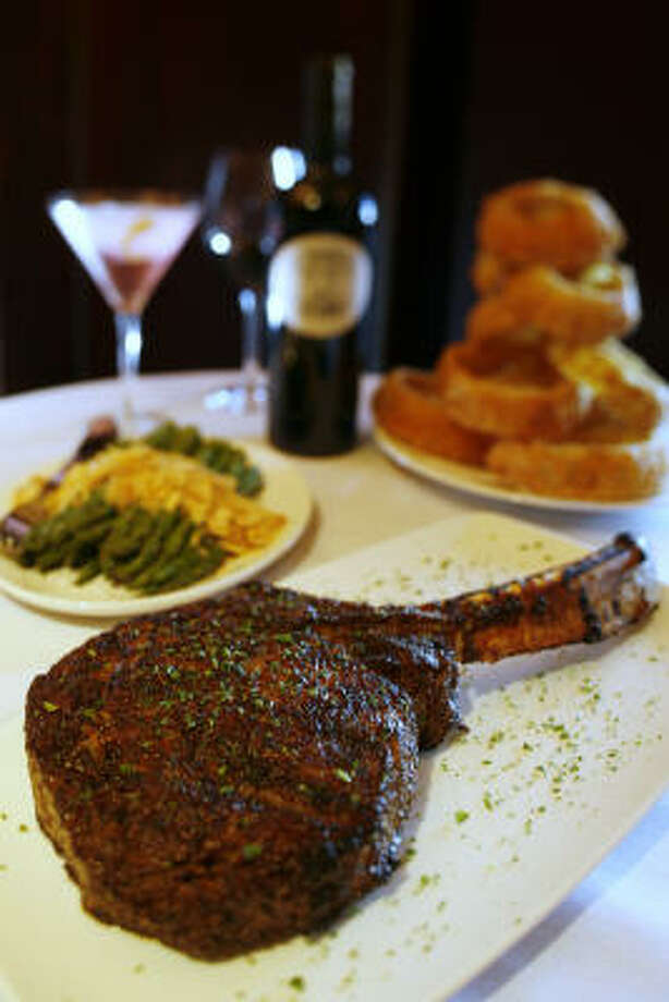Del Frisco's long-bone 32-ounce rib-eye American Kobe is served with asparagus and hand-battered onion rings. Photo: Kevin Fujii, Chronicle
