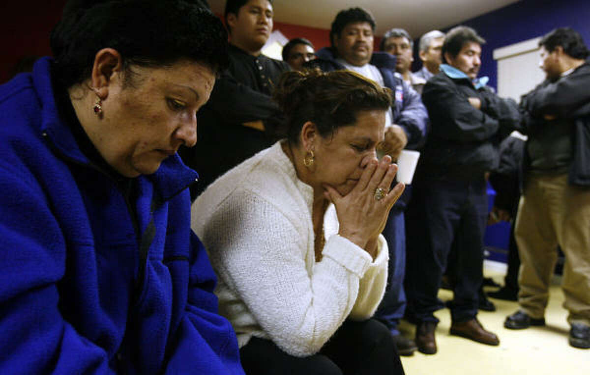 Glenda Vasquez, from left, and Zemalda Martinez mourn at the Waterford Apartments in Clear Lake Wednesday at a service for Sergio Pello.