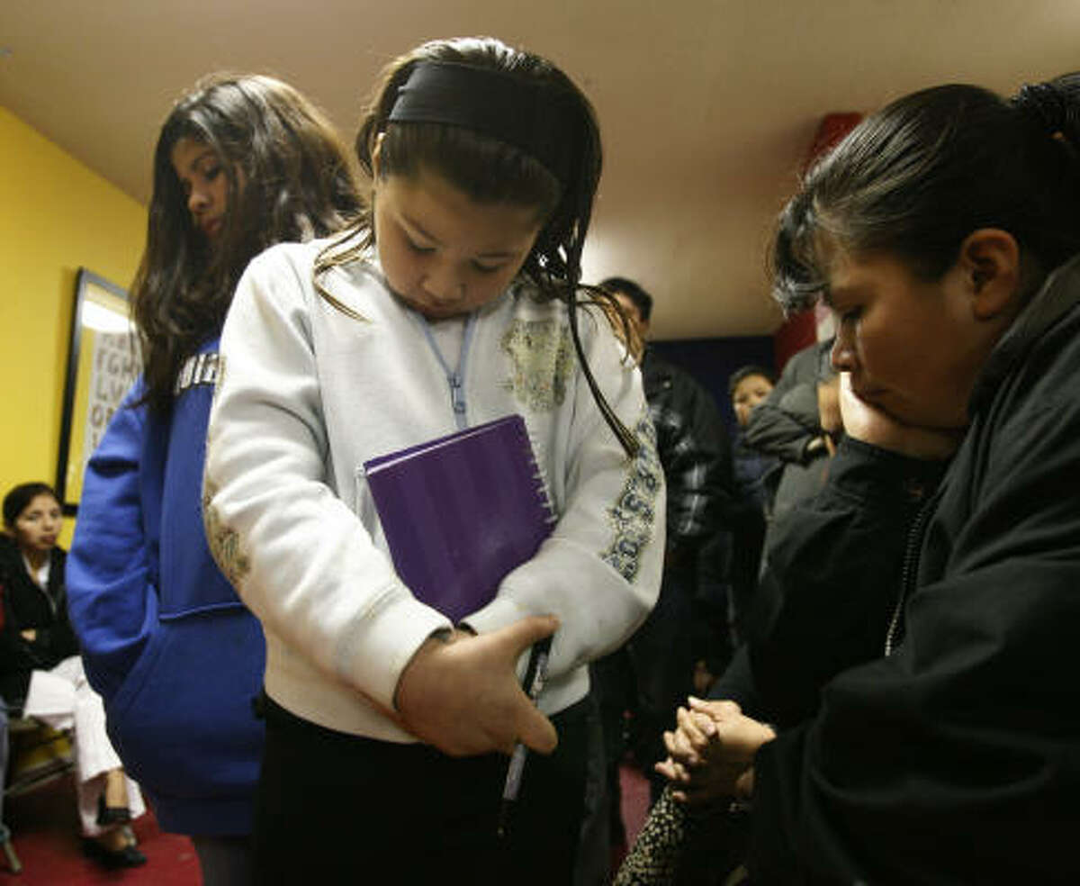 Leydi Hernandez, from left, Helen Hernandez and Barnarda Hernandez pray at the Waterford Apartments in Clear Lake Wednesday during a service for Sergio Pello.