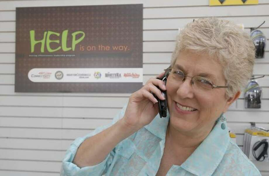 Teri Wathen, a hearing-impaired member of the Houston Commission on Disabilities, tries out a Sprint hearing-aid-compatible phone. Photo: TONY BULLARD, FOR THE CHRONICLE