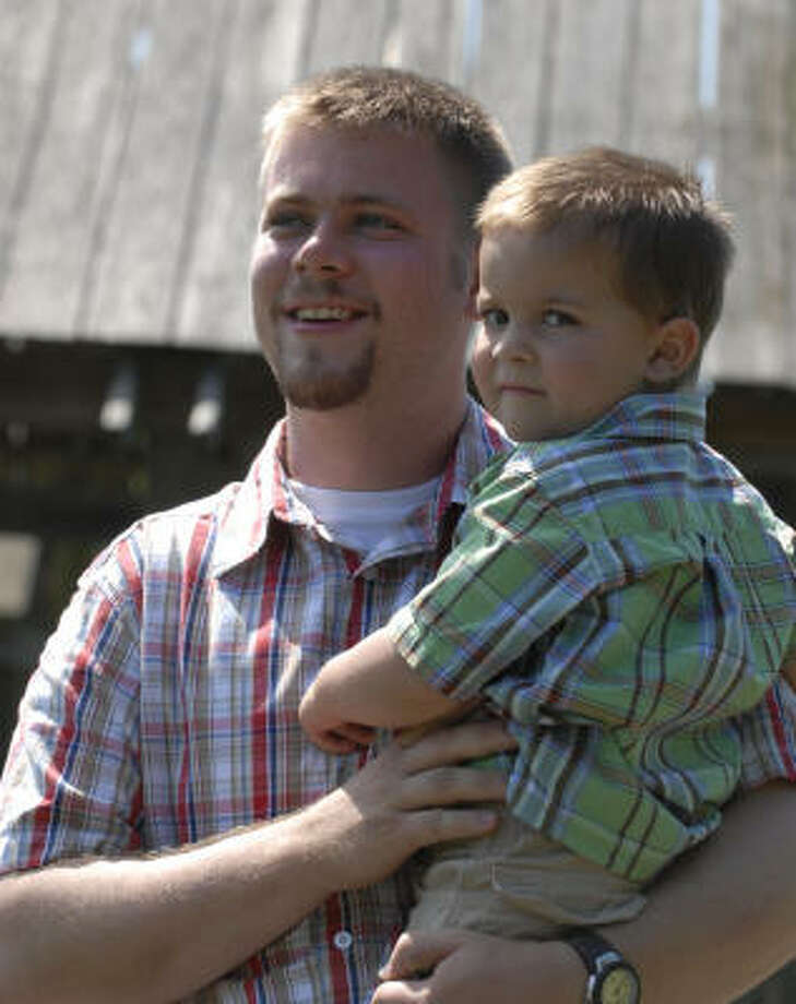 Jeff Blessing, who wiped out on Interstate 45, holds 2½-year-old son, William. Photo: Tony Bullard, For The Chronicle