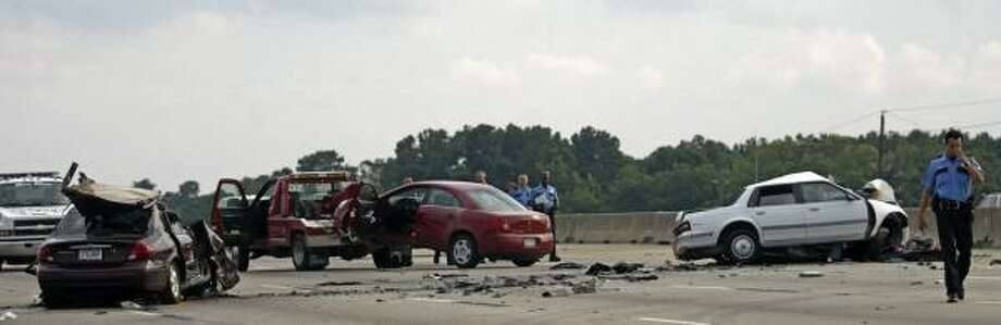 HPD officers investigate a fatal crash on the Eastex Freeway near Beltway 8. Two women were killed and the three children with them were injured when another vehicle collided with their car. That driver also died. Photo: JESSICA KOURKOUNIS, FOR THE CHRONICLE