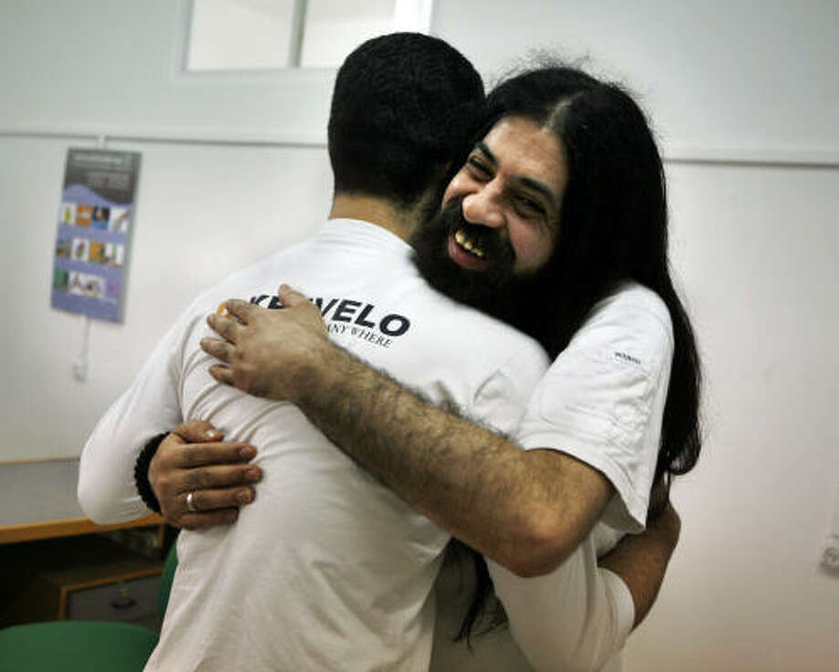 Fatah militant Amjad Halawui, 35, hugs a friend after coming out of seven years in hiding. He and 14 others have signed a nonviolence pledge, taking them off of Israel's wanted list. Photo: KEVIN FRAYER, AP