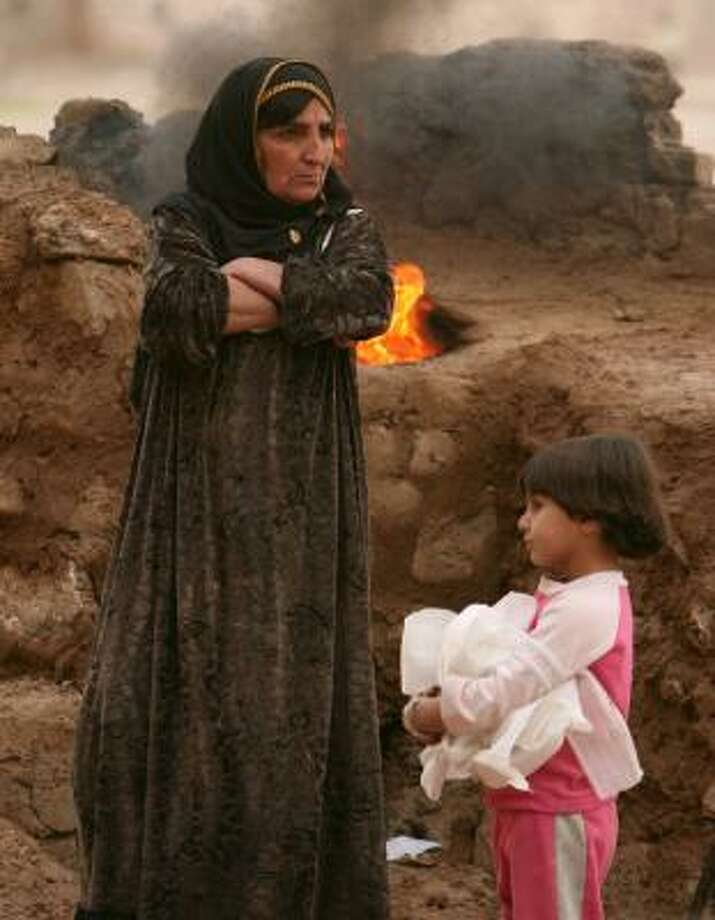 A Kurdish woman and a girl wait for bread to bake at their temporary home in a stadium in Kirkuk last month. Kurds are also waiting for Baghdad to schedule a referendum to resolve their fate. Photo: MICHAEL KAMBER, NEW YORK TIMES