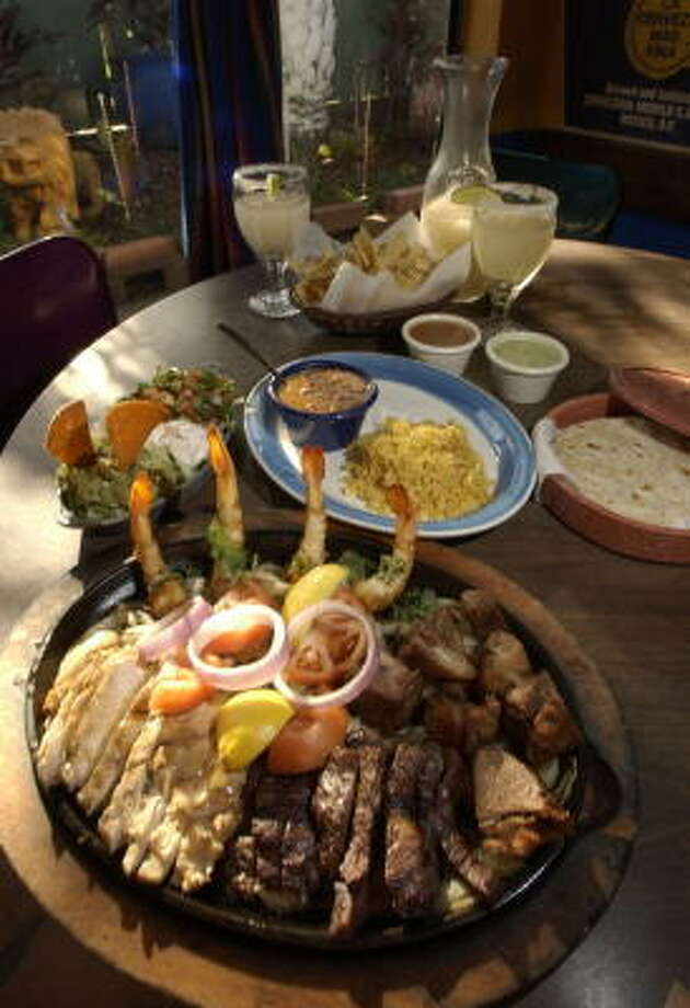 At the original Ninfa's on Navigation, the Mixed Grill Platter is served with beef and chicken fajitas, shrimp and pork. Photo: Ben DeSoto, Chronicle File