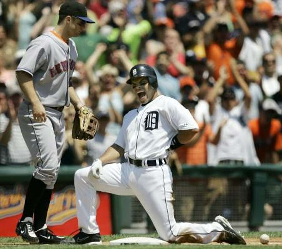 The Tigers' Ivan Rodriguez pays a small price for a two-run triple as the throw to David Wright strikes him in the back. Detroit beat the Mets 15-7 on Sunday. Photo: PAUL SANCYA, ASSOCIATED PRESS