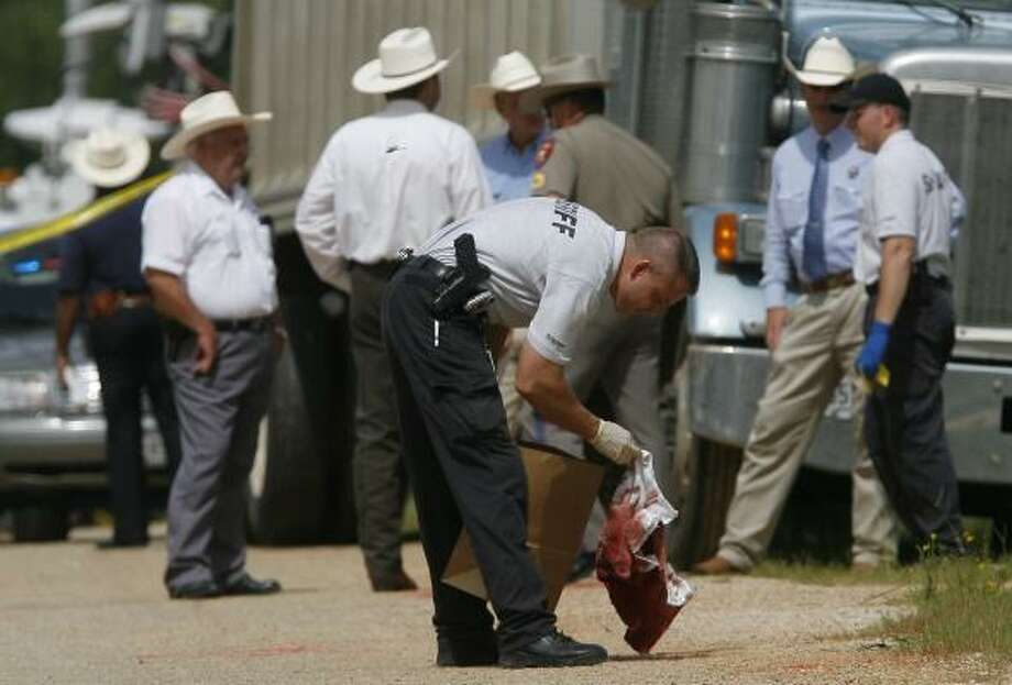 San Jacinto and Montgomery County officers, DPS troopers and Texas Rangers examine evidence at the scene of the violent confrontation Wednesday on Mustang Road in San Jacinto County. Photo: STEVE CAMPBELL, CHRONICLE