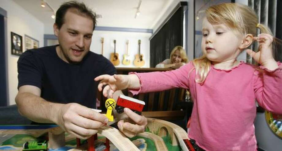 Eban Schletter and 3-year-old daughter Zoe play with Thomas & Friends Wooden Railway toys at Schletter's sound studio in Los Angeles. After returning a recalled Thomas toy, the family received a replacement, which was also recalled. Photo: DAMIAN DOVARGANES, ASSOCIATED PRESS