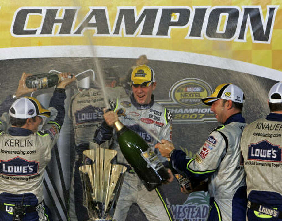 Driver Jimmie Johnson , center, and crew chief Chad Knaus, right, celebrate Johnson's Nextel Cup Championship victory at the Homestead-Miami Speedway in Homestead, Fla. Photo: Alan Diaz, AP