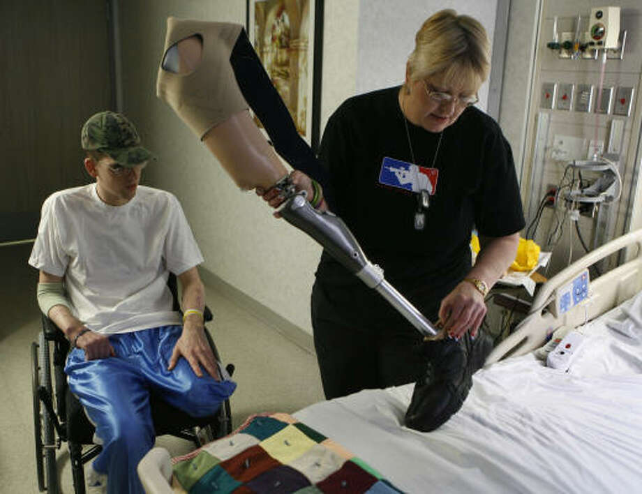 Iraq War veteran Robert Engelbrecht and his mother, Raylene Watts, take a look at his new prosthetic leg. The soldier sustained a brain injury, amputation, loss of vision in one eye and other medical problems from a bomb blast in Iraq. Photo: Carlos Antonio Rios, Chronicle
