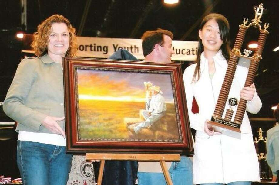 Ronda Landers, left, Cinco Ranch HIgh School art teacher, shares the excitement with Wenjun ``Jane'' Liu, 18, who won reserve grand champion for her oil painting.