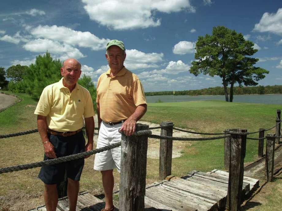 """Justin Curren, left, and Willie Wiginton, the current and immediate past president of the Waterwood Community Association, respectively. They're standing in front of the green of the signature par-3 14th, known as """"The Cliffs."""" Photo: Mike Bailey"""