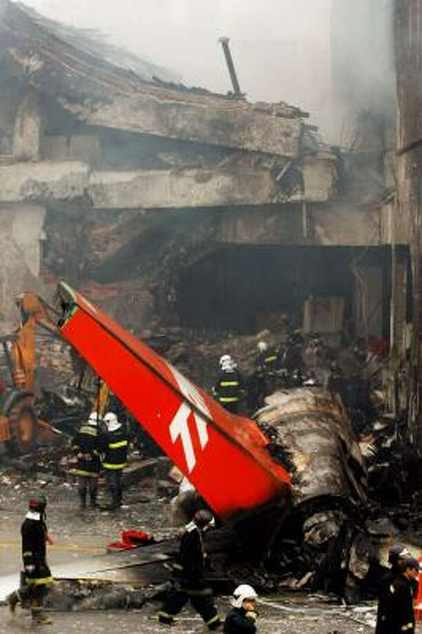 Firefighters work at the site where a TAM airlines commercial jet crashed in Sao Paulo, Brazil today. Photo: Andre Penner, AP