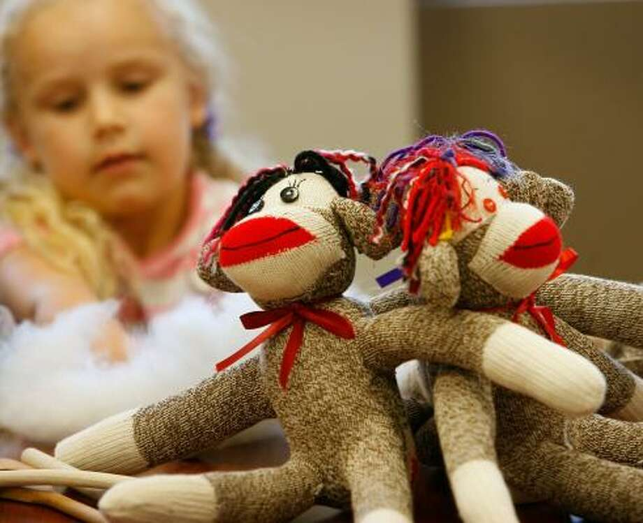 Christ United Methodist Church volunteers, such as Maia Catteral, 5, make and send sock monkeys to children who are in need of comfort. Photo: KEVIN FUJII, CHRONICLE