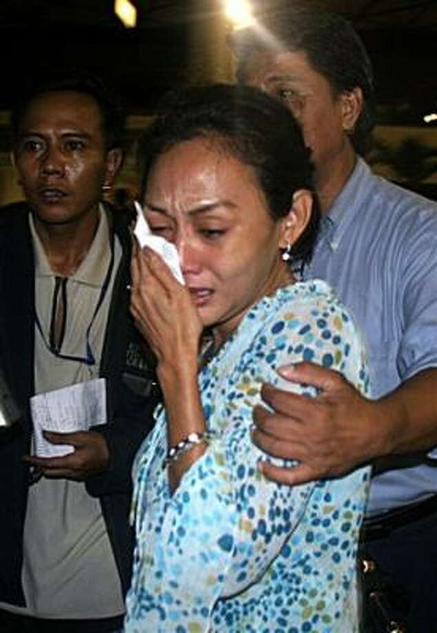 An unidentified relative of a passenger who was aboard an Indonesian passenger jet weeps as she waits for news at the airport in Surabaya, Indonesia, today. Photo: HENDRA PRADANA, AP