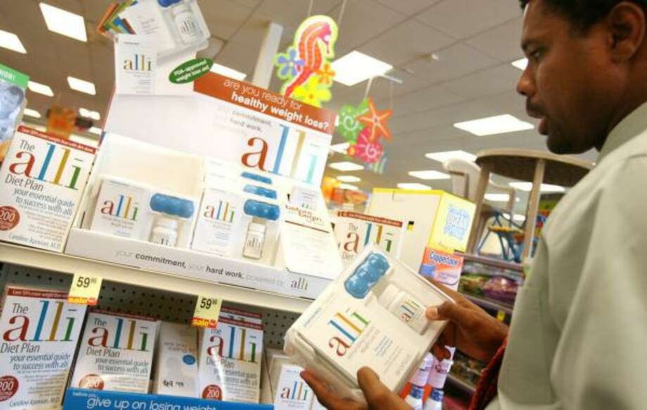 CVS store manager Warren Barrett restocks Alli at his store on Waugh and Dallas this week. Several local stores quickly sold out. Photo: SHARÓN STEINMANN, CHRONICLE
