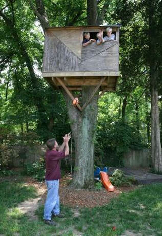 In the Connolly's Bethesda, Md., backyard, Grant, 8, Quinn, 3, and Evan, 10, toss a football to dad Paul from their treehouse. Photo: WILLIAMSON, WASHINGTON POST
