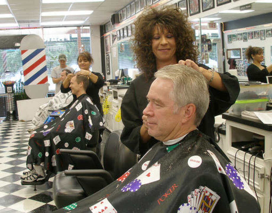 Annette Brogdon, owner of the Northpark Barber Shop, standing front, and barbers Rose Colom and Wade Burns, keep the traditions of the small-town barber shop alive. Photo: Harry Williamson, For The Chronicle