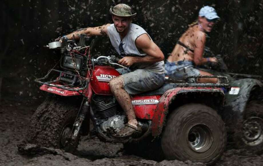 Larry Robichaux and Tonya Caldwell, of Baton Rouge, La., get dirty on all-terrain vehicles during the Texas Redneck Games at the Pool Ranch in Athens on Saturday. Photo: NICOLE FRUGE, SAN ANTONIO EXPRESS-NEWS