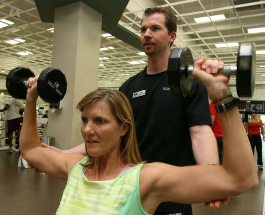 Teresa Swanson, 42, lifts 15-pound hand weights as Jason Hodge, 30, personal trainer assists at Life Time Fitness in Katy. Photo: Suzanne Rehak, For The Chronicle