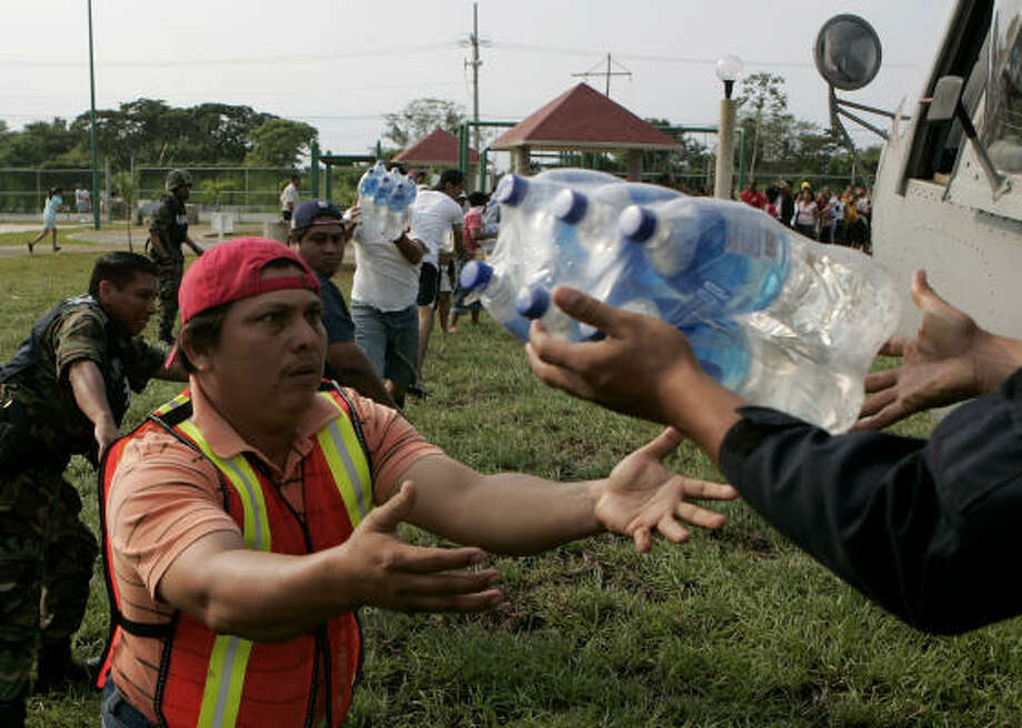 Volunteers carry bottles of water for flood victims in Villahermosa today. Photo: Eduardo Verdugo, AP