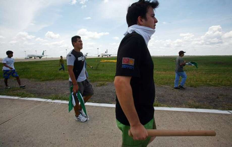 Protesters prowl the runway at Viru Viru airport Friday. Thousands responded to the provincial governor's plea to retake the facility. Photo: DADO GALDIERI, ASSOCIATED PRESS