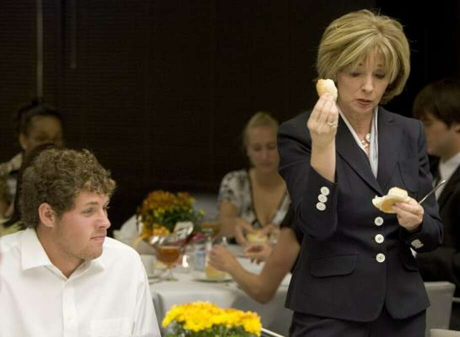 Image consultant Helen Perry shows Rice University seniors the proper way to eat bread. Photo: Brett Coomer, Chronicle
