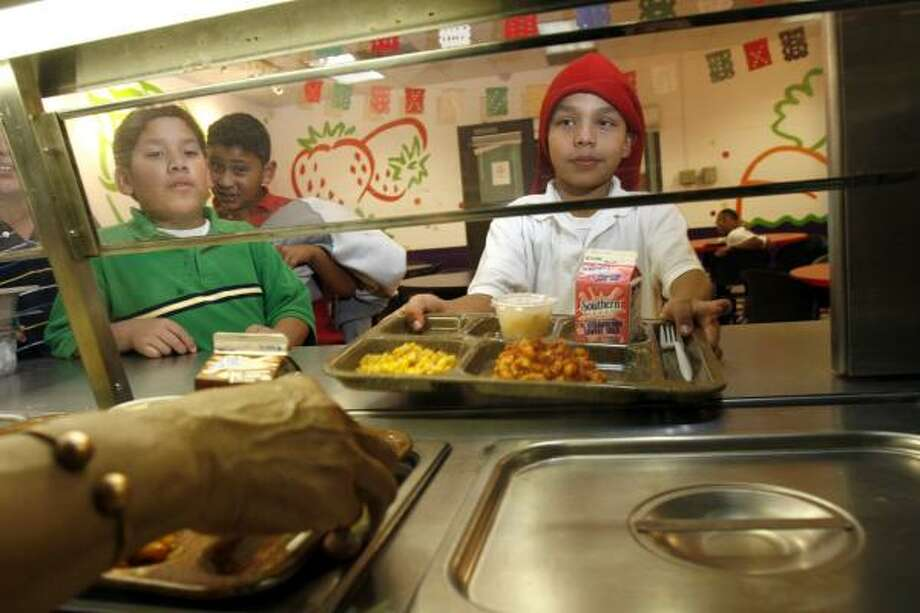 Jason Flores, 10, left, and Christian Navarro, 9, right, are served an early dinner at the Kids Cafe at the Boys & Girls Club of Greater Houston's Shell Unit. Photo: JOHNNY HANSON, FOR THE CHRONICLE