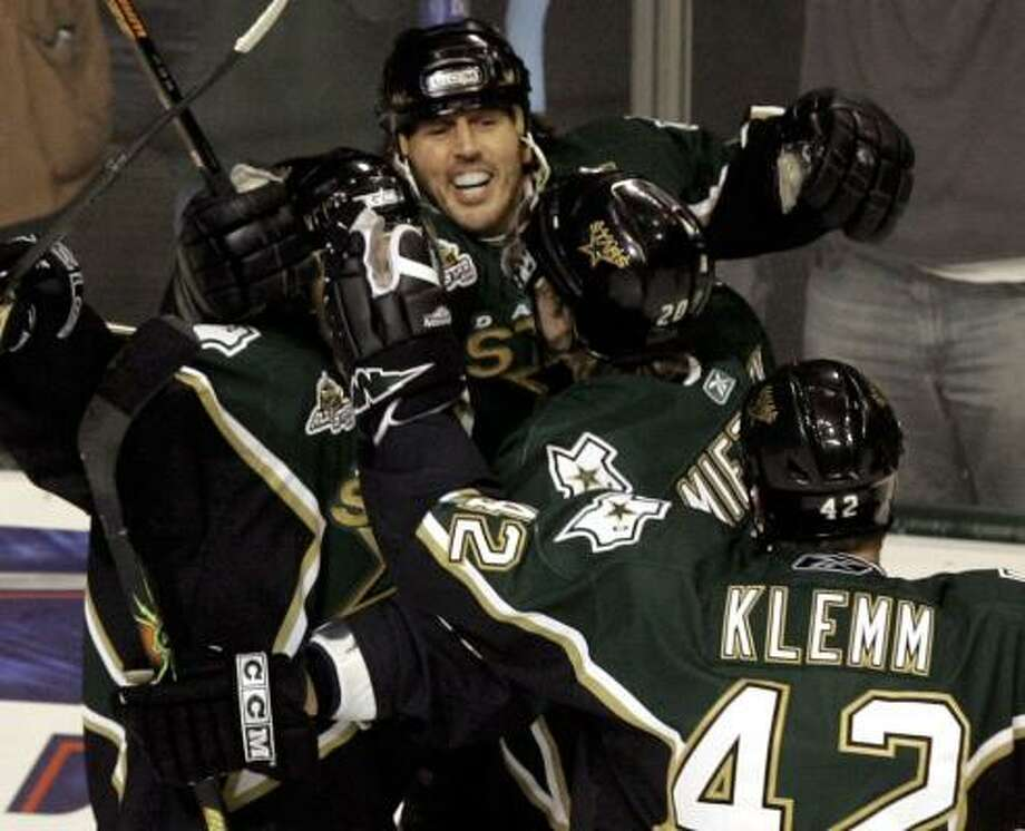 Mike Modano, center, is mobbed by teammates after becoming the 39th player to score 500 NHL goals. Photo: LM OTERO, ASSOCIATED PRESS