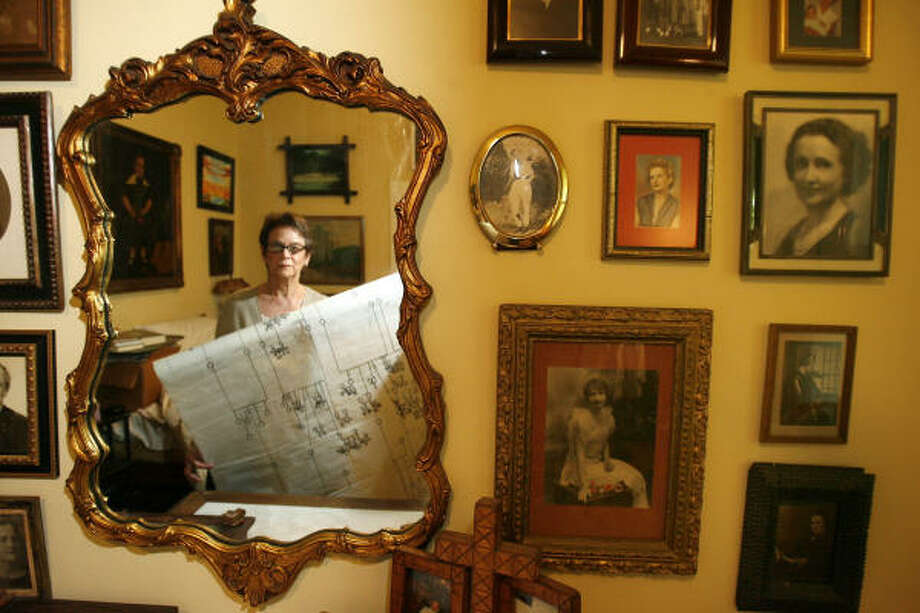 Holding a hand-drawn family tree, Victoria Harrison is reflected in a mirror next to family photos. Photo: SHARÓN STEINMANN, HOUSTON CHRONICLE