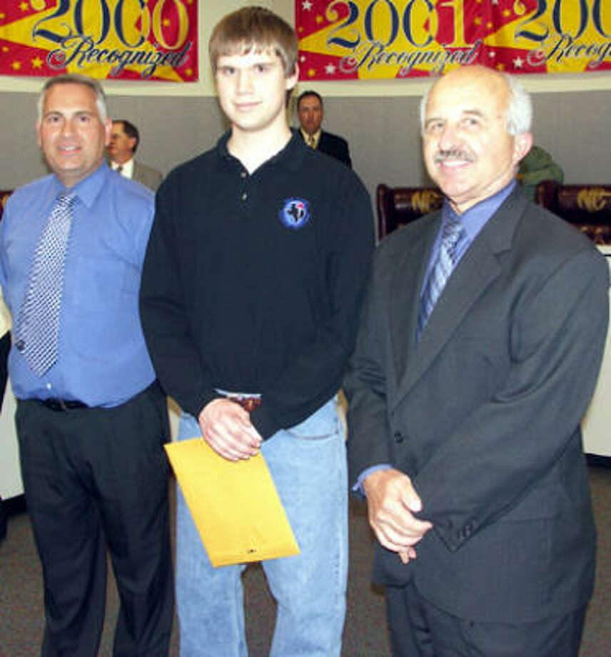 New Caney High School junior Kevin Bush, center, was recognized by trustees recently for academic achievement. With Bush are New Caney High School principal John Yonker, left, and board president Gene Gregory, right. Photo: Suzanne West