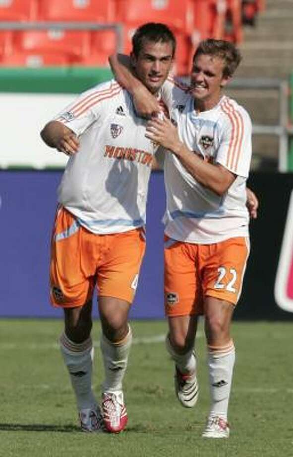 The Dynamo's Patrick Ianni, left, and Stuart Holden celebrate after hooking up on the game-winning goal against the Wizards at Kansas City, Mo. Photo: Dick Whipple, AP