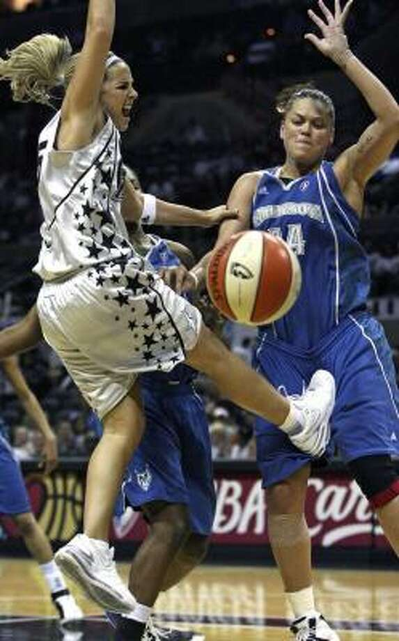 The Silver Stars' Becky Hammon, left, loses the basketball, but it was hard for Minnesota Lynx defender Kristen Mann to feel too good about it while she's being kicked. Photo: TOM REEL, AP