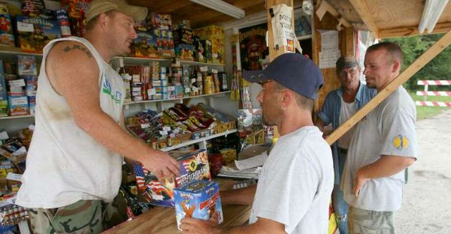 Mark Cochrell, from left, Les Magee, Ron Cochrell and Matt Rodriguez prepare for the July 3rd and 4th crowds at one of the many fireworks stands on Louetta Road. Photo: Bill Olive, For The Chronicle