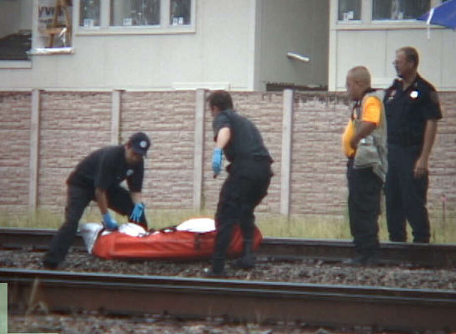 Medical examiners remove the body of a man found dead this afternoon on the train tracks near Congress and Dowling. Photo: Lindsay Meeks, For The Chronicle