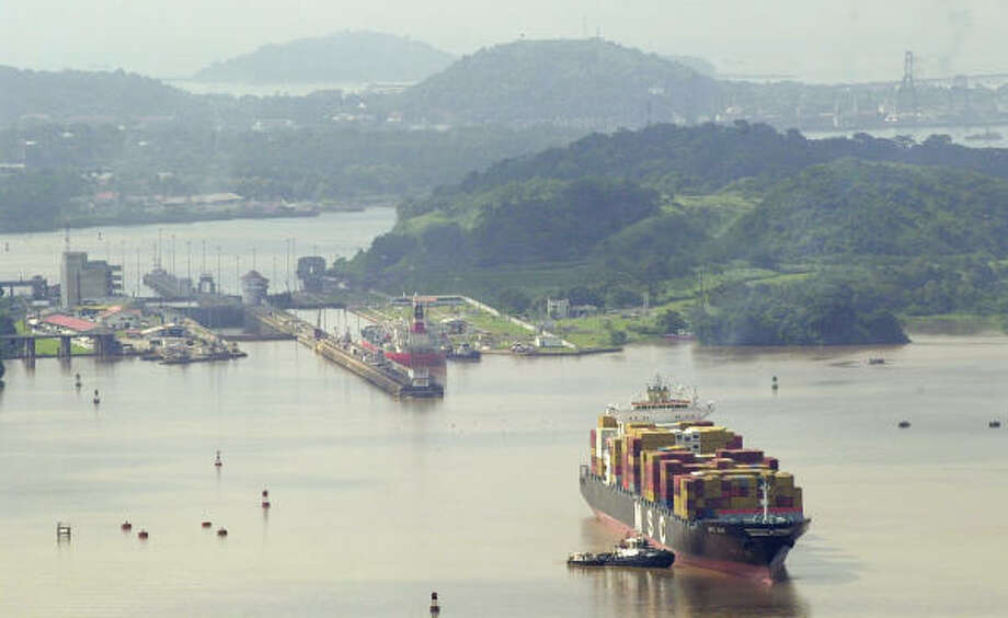 A container ship is escorted by a tugboat through the Miraflores Lake in the Panama Canal. Photo: ARNULFO FRANCO, Associated Press
