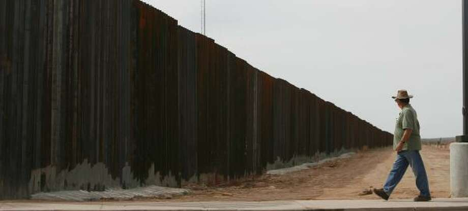 A man walks on the U.S. side of the border with Mexico in October. U.S. officials have vowed to complete nearly 400 miles of border fence by the end of 2008. Photo: SHARÓN STEINMANN, CHRONICLE