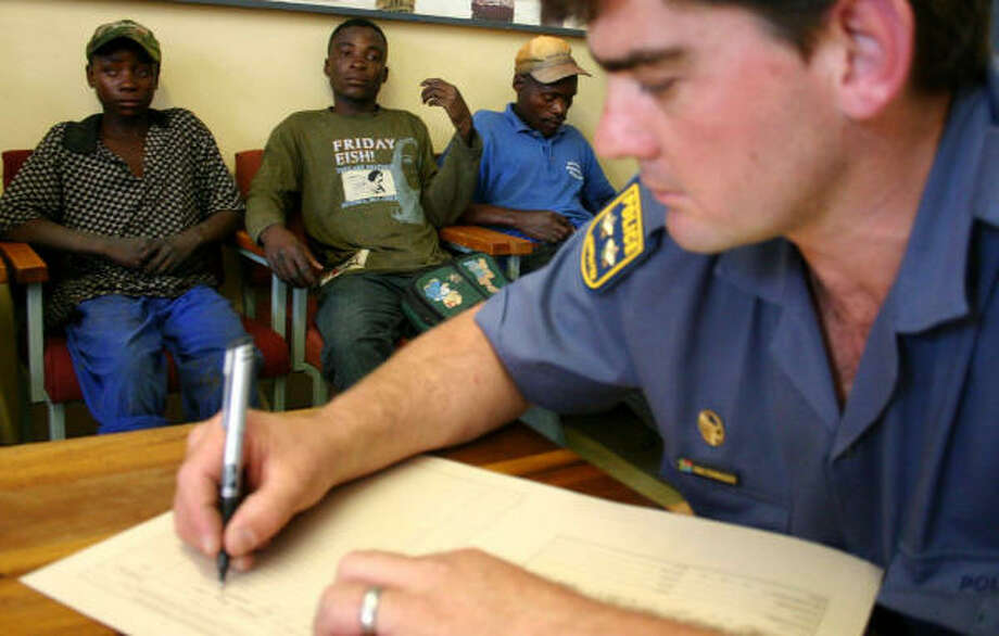 A police officer fills out arrest records in November for three suspected gold smugglers in Welkom, South Africa. The world's top gold producer has launched a crackdown against smugglers, who live for months in the bowels of abandoned pits, plundering gold worth millions. Photo: FATI MOALUSI, AFP/Getty Images