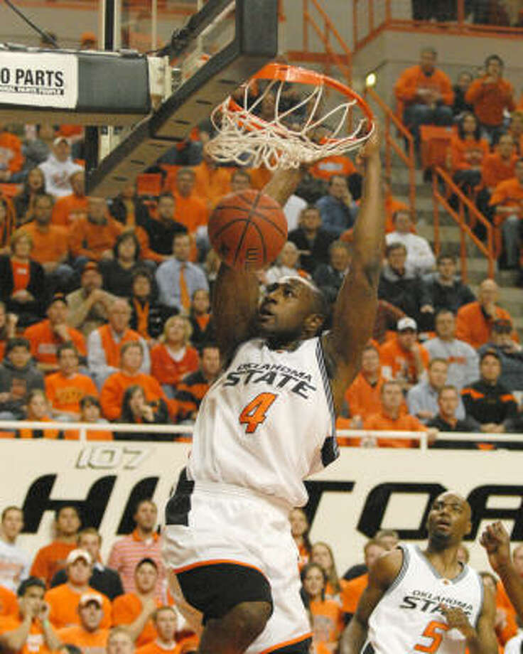 Oklahoma State forward Mario Bogan (4) dunks against Texas, while teammate Marcus Dove (5) looks on during the first half in Stillwater, Okla. Photo: Brody Schmidt, AP